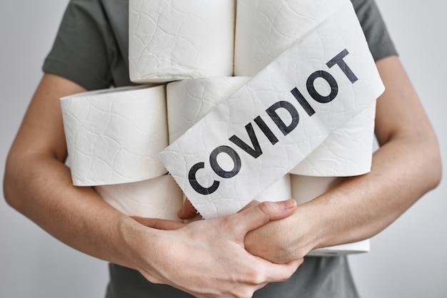 Homem detém muitos rolos de papel higiênico com inscrição covidiot. conceito de pânico de coronavírus covid-19
