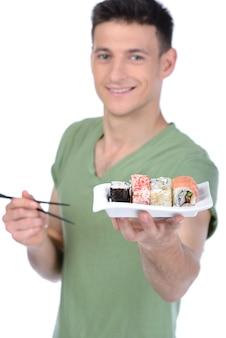 Homem detém sushi na mão e sorri.