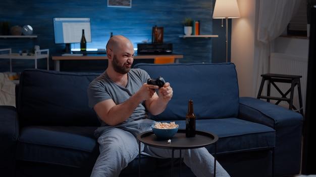 Homem determinado e animado sentado no sofá jogando videogame
