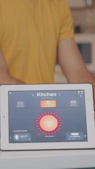Homem digitando em um laptop trabalhando em casa com sistema de iluminação de automação usando aplicativo controlado por voz no tablet, acendendo a luz