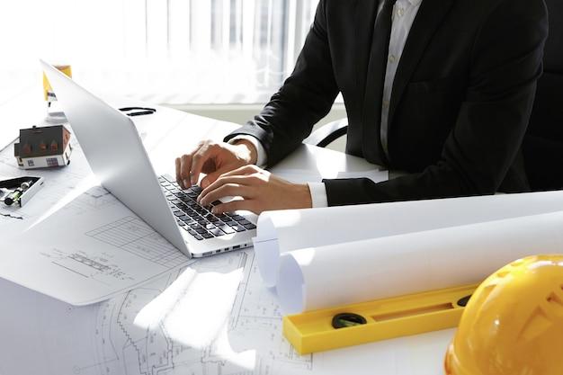 Homem digitando no laptop ao lado de ferramentas de engenharia