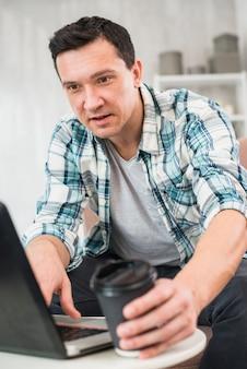 Homem digitando no laptop e tomando o copo da bebida em casa