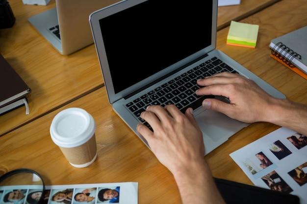 Homem digitando no laptop na mesa