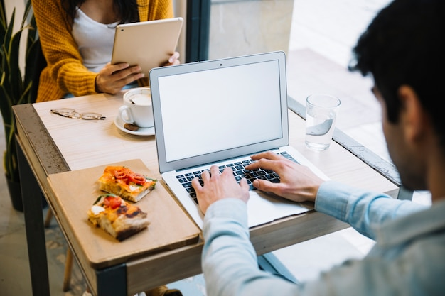 Homem digitando no laptop no café