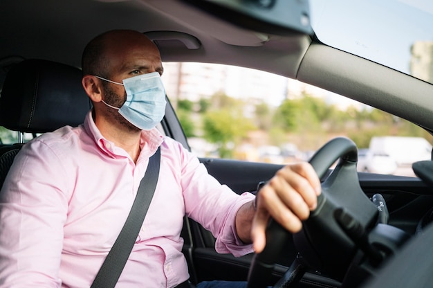 Homem dirigindo carro com máscara protetora