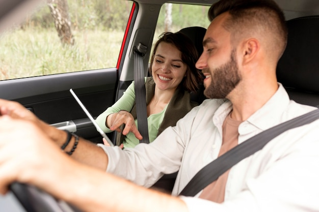 Homem dirigindo e olhando para o tablet da namorada