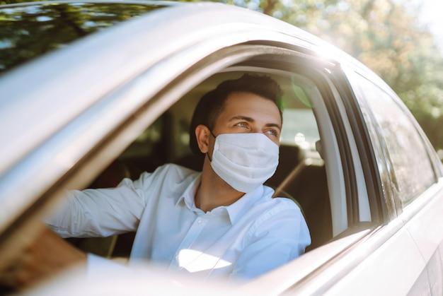 Homem dirigindo um carro coloca uma máscara médica durante uma epidemia na cidade de quarentena.
