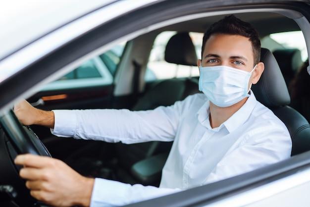 Homem dirigindo um carro com máscara protetora durante a cidade de quarentena. covid 19.