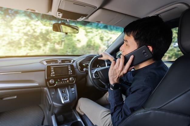 Homem dirigindo um carro e falando ao celular