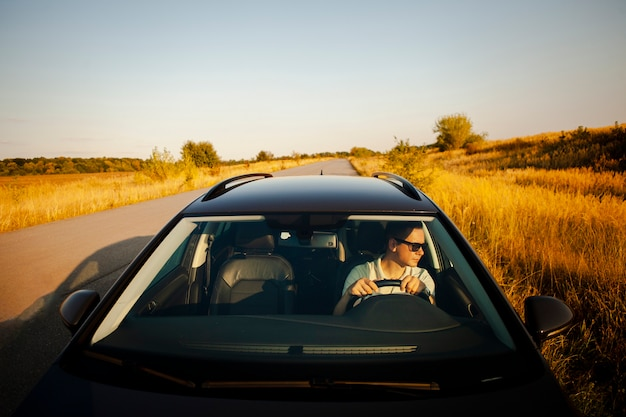 Homem dirigindo um carro preto