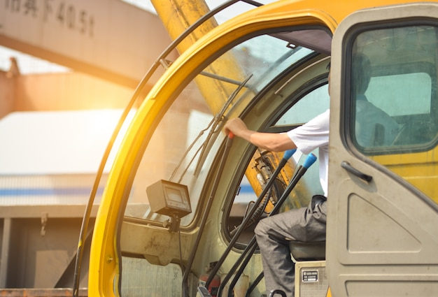Homem dirigindo um guindaste para levantar alguns equipamentos