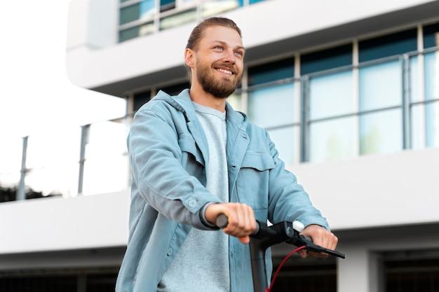 Homem dirigindo uma scooter ecológica ao ar livre