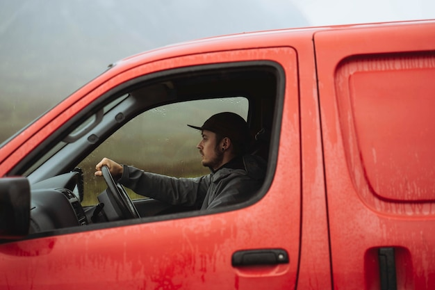 Homem dirigindo uma van vermelha enquanto chove