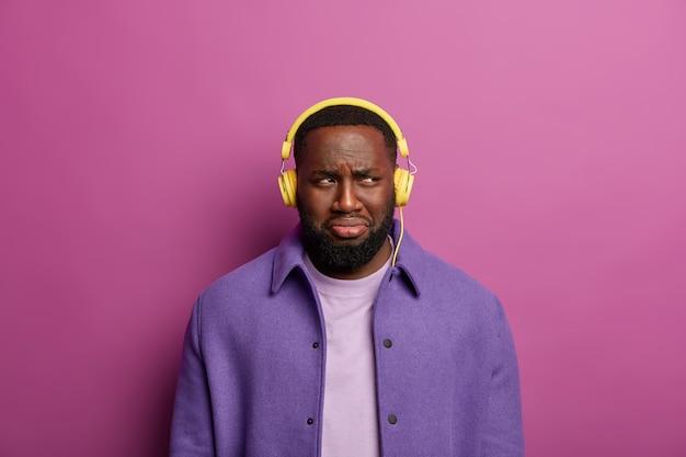 Homem discotente chateado porque algo deu errado com seus fones de ouvido, não consegue ouvir música, olha tristemente de lado, tem expressão facial sombria