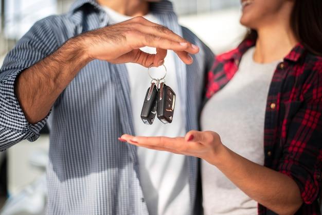 Homem distribuindo as chaves do carro para mulher