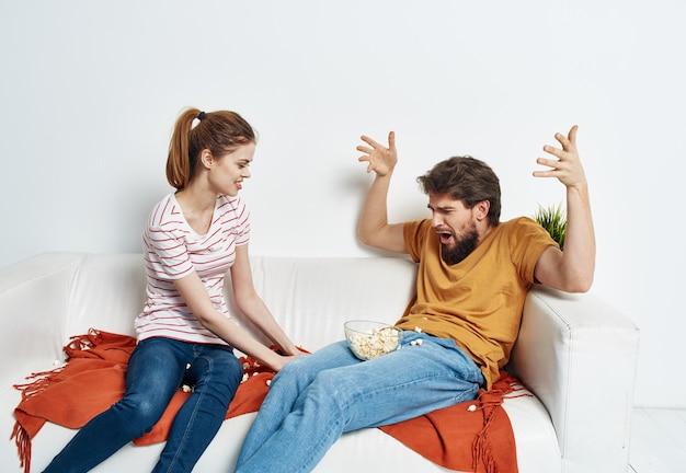 Homem divertido e mulher enérgica assistindo tv no sofá
