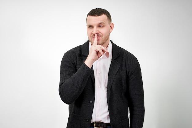Homem dizendo silêncio e ficar quieto com o dedo nos lábios gesto