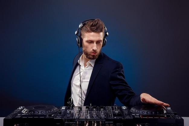 Homem dj de terno escuro tocando música em um estúdio de mixagem de djs em um espaço azul escuro