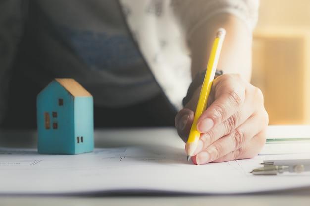 Homem do arquiteto que guarda o lápis que trabalha com portátil e modelos para o plano arquitetónico, coordenador que esboça um conceito do projeto de construção e da propriedade.