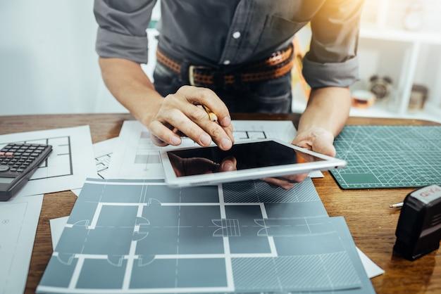 Homem do arquiteto que trabalha com papel e modelos para o plano arquitetônico da construção nova da construção que esboça o conceito.