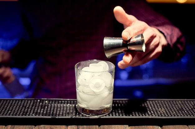 Homem do barman do clube noturno fazendo um coquetel em um copo com gelo.