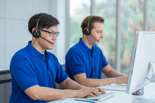 Homem do centro de chamada no uniforme azul da camisa que trabalha o atendimento ao cliente que veste o auscultadores que fala com um cliente no escritório do centro de chamada.