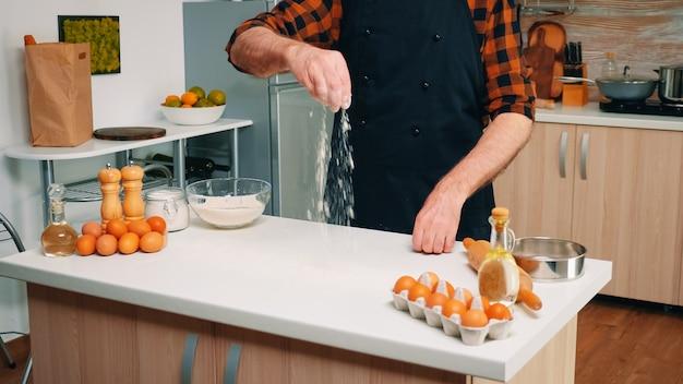 Homem do chef sênior tirando farinha da tigela de vidro e peneirando na mesa. padeiro sênior aposentado com bonete e uniforme polvilhando, peneirando e espalhando ingredientes refogados assando pizzas e pães caseiros.