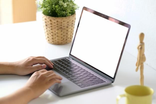 Homem do espaço de trabalho que trabalha com seu portátil na mesa.