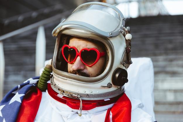 Homem do espaço lgbt em uma estação futurística homem com traje espacial caminhando em uma área urbana