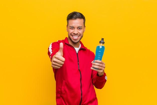 Homem do esporte asiático do sul jovem segurando uma bebida energética.