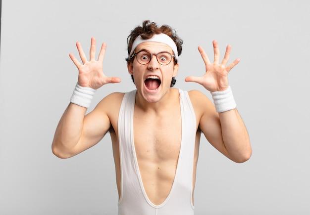 Homem do esporte bem humorado gritando em pânico ou raiva, chocado, apavorado ou furioso, com as mãos perto da cabeça