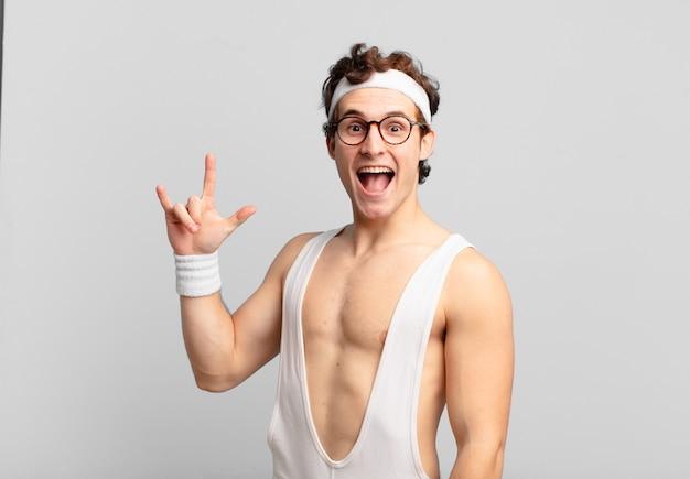 Homem do esporte bem-humorado se sentindo feliz, divertido, confiante, positivo e rebelde, fazendo sinal de rock ou heavy metal com a mão