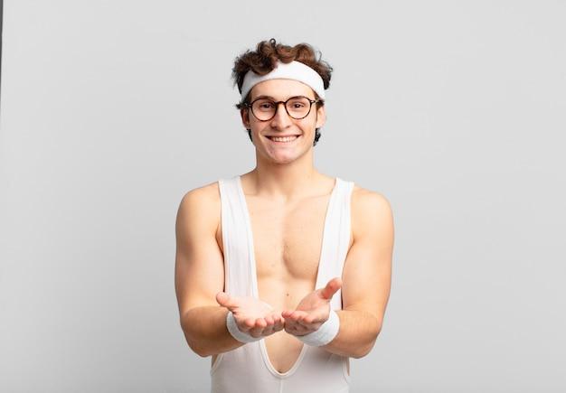 Homem do esporte bem-humorado, sorrindo feliz com um olhar amigável, confiante e positivo, oferecendo e mostrando um objeto ou conceito
