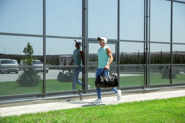 Homem do esporte contra edifício envidraçado moderno, aeroporto em megapolis