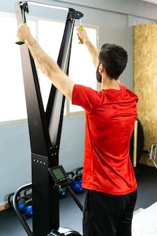 Homem do esporte fazendo exercícios na máquina de simulação do esquiador na academia