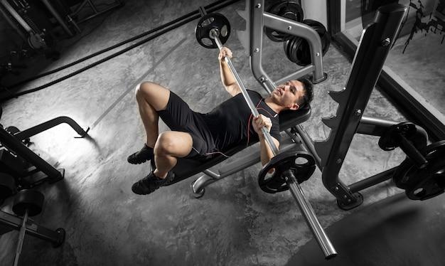 Homem do esporte treinando com uma barra pesada na academia