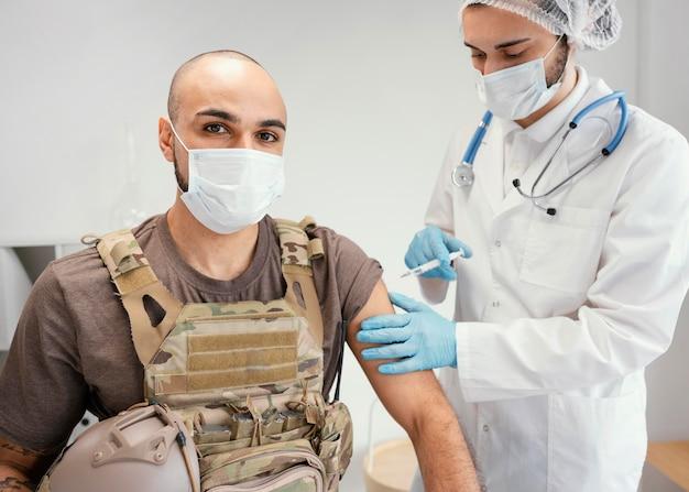 Homem do exército sendo vacinado