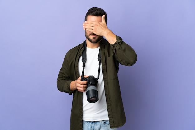 Homem do fotógrafo sobre a parede roxa isolada que cobre os olhos pelas mãos. não quero ver algo