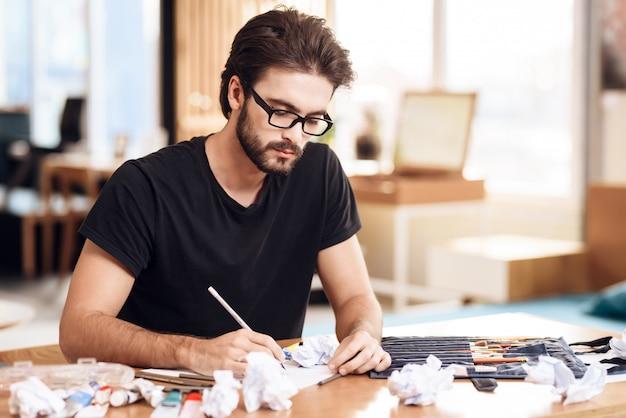 Homem do freelancer que tira com o lápis no papel que senta-se na mesa.