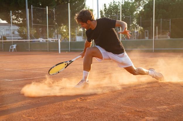 Homem do jogador de tênis profissional que joga na corte na tarde.