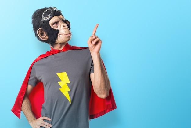 Homem do macaco do super-herói apontando para cima no fundo colorido