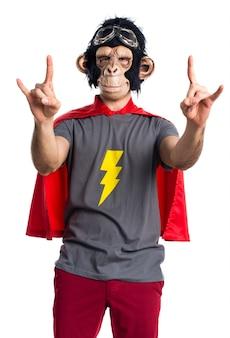 Homem do macaco do super-herói que faz o gesto do chifre
