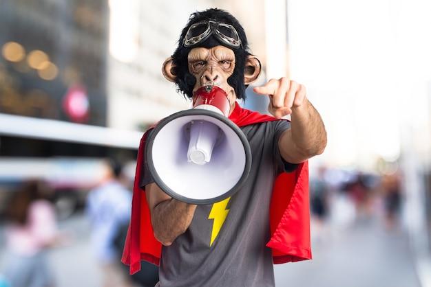 Homem do macaco do super-herói que grita por megafone em fundo não focado