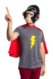 Homem do macaco do super-herói tocando na tela transparente