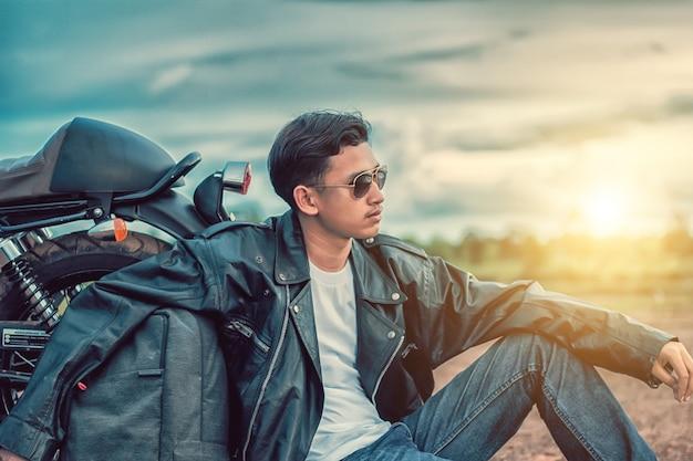 Homem do motociclista que senta-se com seu velomotor ao lado do lago natural e bonito.