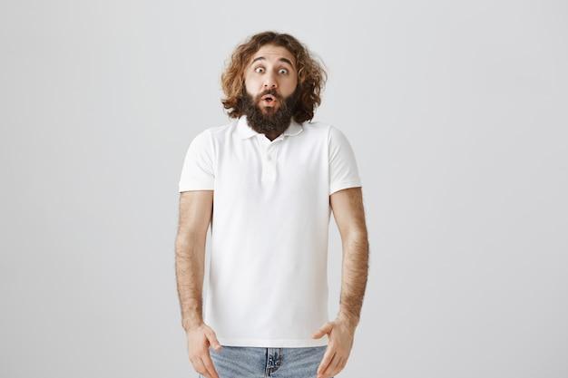 Homem do oriente médio assustado parece surpreso, ofegante e de queixo caído em estado de choque