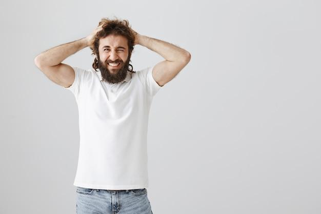Homem do oriente médio frustrado e chateado, jogando cabelo e fazendo careta, tem problemas