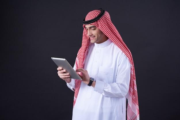 Homem do oriente médio que levanta usando a tabuleta isolada.