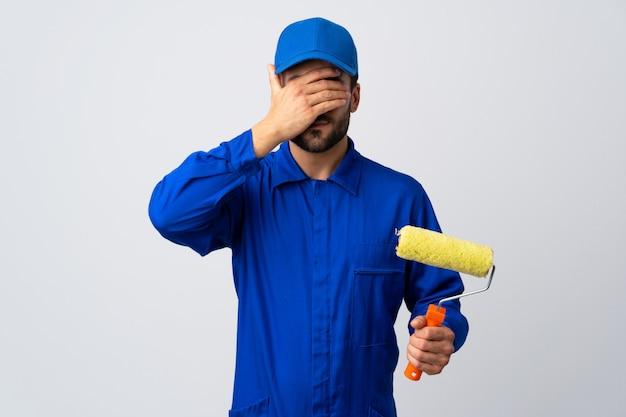 Homem do pintor que mantém um rolo de pintura isolado na parede branca que cobre os olhos pelas mãos. não quero ver algo