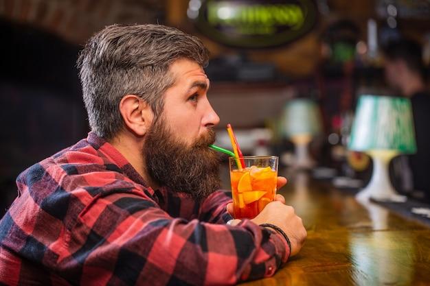 Homem do retrato, bebendo suco de laranja. coquetel de homem barbudo.